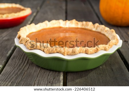 Freshly baked pumpkin pies cooling on rough wood boards. Green and red ceramic pie plates. Fresh pumpkin in the background. - stock photo