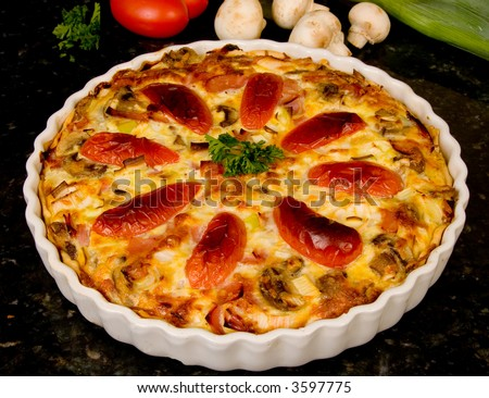 Freshly Baked Quiche Lorraine with tomatoes and mushrooms in background - stock photo