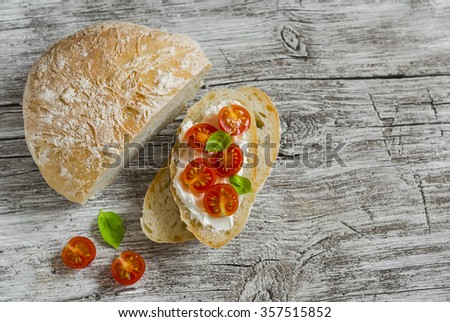 Freshly baked rustic bread and  sandwich with ricotta, tomato and basil on a light wooden board - stock photo