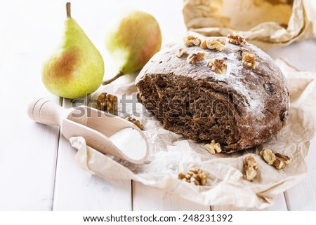 Freshly baked rye sourdough bread with walnuts and pears on wooden background. Selective focus, shallow Depth of Field - stock photo