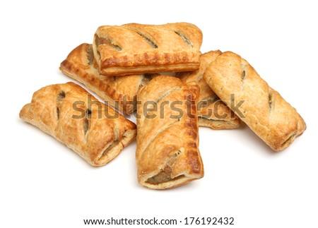Freshly baked sausage rolls on white background - stock photo