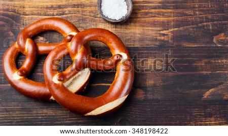 Freshly baked soft pretzel from Germany on wooden background - stock photo
