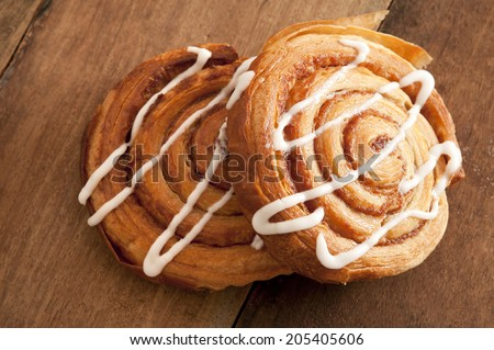 Freshly baked spiral Danish pastries with flaky puff pastry filled with apple or almond paste and drizzled with white icing for a delicious sticky sweet snack or dessert - stock photo