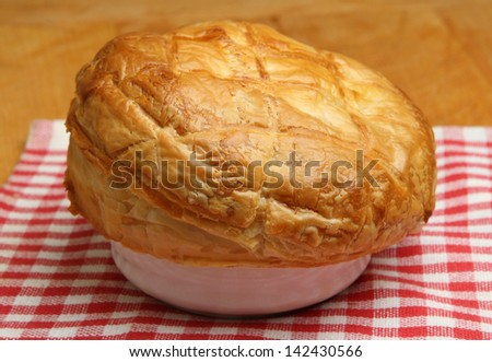 Freshly baked steak pie resting on tea towel. Shallow DoF, focus at centre of image. - stock photo