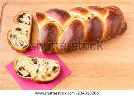Freshly baked sweet braided bread loaf with fruits and nuts. - stock photo