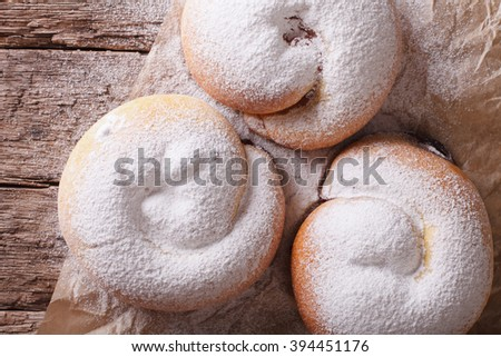 freshly baked sweet rolls ensaimadas with powdered sugar close-up on the table. Horizontal view from above - stock photo