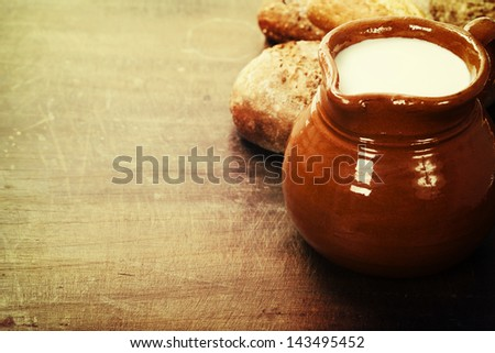 Freshly baked traditional bread and milk on wooden table