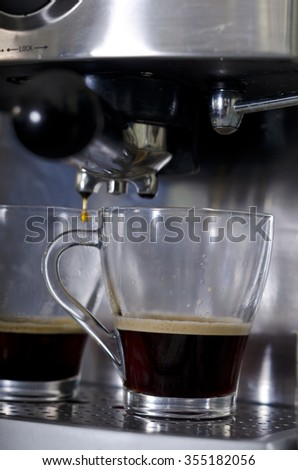 Freshly brewed coffee dripping into two glass cups on coffee machine. Focus is on one glass cup with third full of black coffee. coffee machine has polished metal parts.