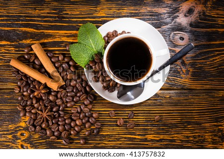 Freshly brewed cup of espresso coffee with roasted whole coffee beans, mint, star anise and stick cinnamon spices on a rustic wooden table, overhead view - stock photo