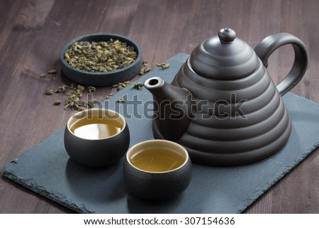 freshly brewed green tea in ceramic ware on wooden table, horizontal - stock photo