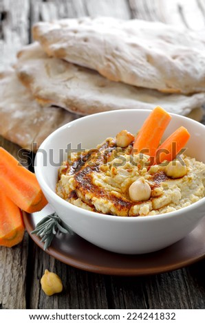 Freshly cooked chickpea hummus served with pita and carrots, decorated with olive oil and paprika powder - stock photo