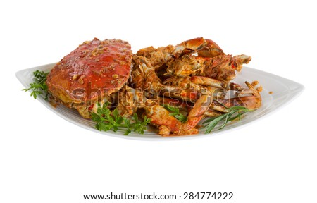 Freshly cooked crab with spicy sauce and herbs on serving plate. Isolated on white background with selective focus towards front.  - stock photo