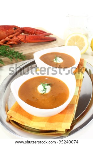 freshly cooked lobster soup with lemon, dill and cream dollop - stock photo