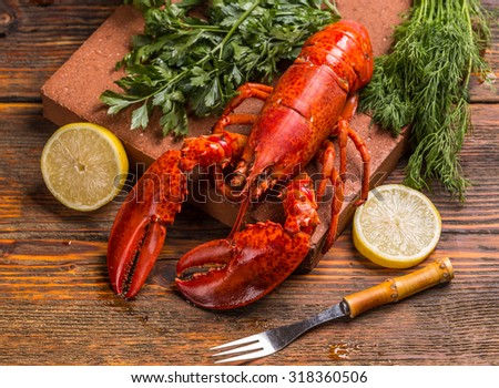 Freshly cooked lobsters with lemon and herbs - stock photo