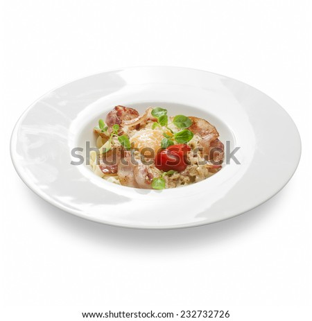 Freshly cooked pasta with salami, ham egg and cheese on a plate on a white background. - stock photo