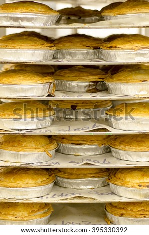 Freshly cooked pies just out of the oven on shelves - stock photo