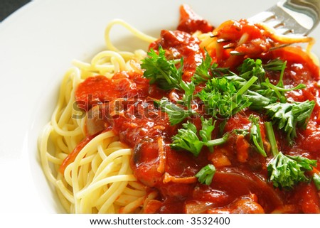 Freshly cooked plate of spaghetti with seafood sauce sprinkled with fresh green herbs. - stock photo