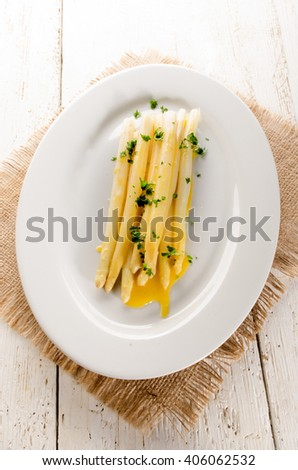 freshly cooked white asparagus with melted butter and chopped parsley on a plate - stock photo