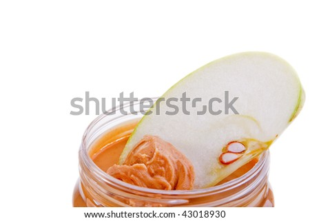 Freshly cut apple slice scooping peanutbutter in a jar - shallow DOF on apple slice, isolated - stock photo