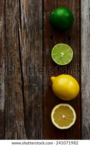 freshly cut half and whole lemons and limes on rustic wooden texture. Top view. - stock photo
