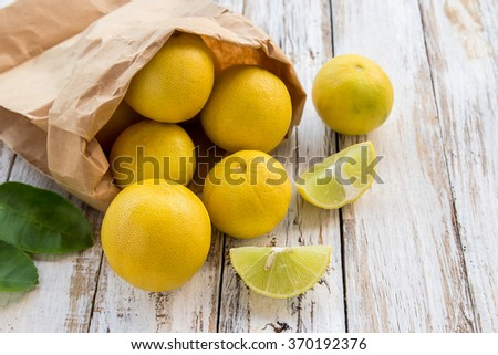 Freshly cut half and whole lemons in paper bag on white wooden table background - stock photo