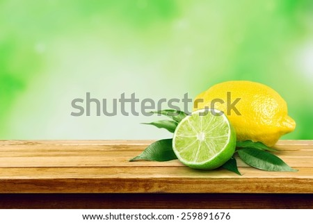 Freshly cut half and whole lemons on rustic boards  - stock photo