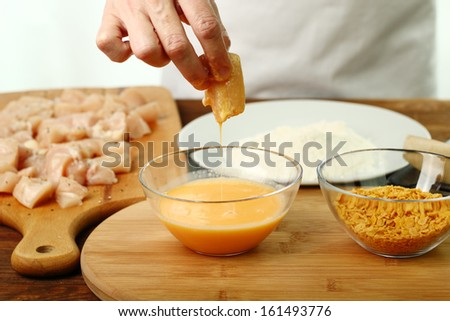 Freshly egged chicken fillet. Making oven baked corn flake crumbs chicken nuggets. Series. - stock photo