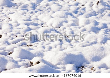 Freshly fallen fall autumn snow covering ground with smooth round shapes of cobble stone and gravel starts to thaw quickly - stock photo