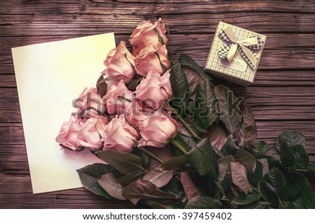 Freshly gathered pink stemmed roses on top of blank white paper with pretty little bowed gift box over weathered wooden background