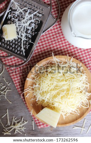 Freshly grated parmesan and cheddar cheese on a wooden board and grater and fresh milk pot  - stock photo
