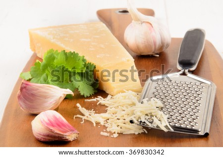 freshly grated parmesan cheese on a wooden board with parsley and garlic - stock photo