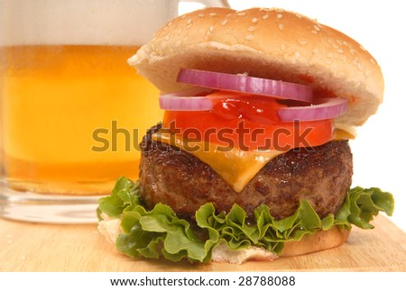 Freshly grilled cheeseburger with a cold beer - stock photo