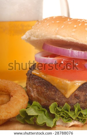 Freshly grilled cheeseburger with onion rings and beer - stock photo