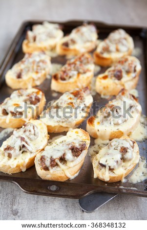 Freshly grilled french loaf bread topped with chicken livers and mozzarella cheese