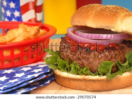 Freshly grilled hamburger in a 4th of July setting - stock photo