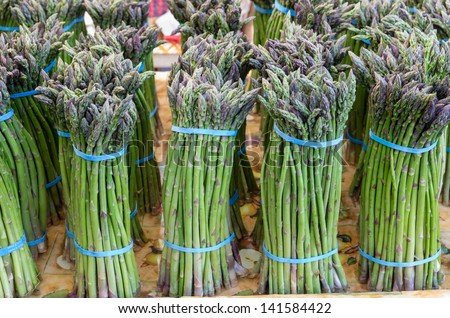 Freshly harvested asparagus bunches on display at the farmers market - stock photo