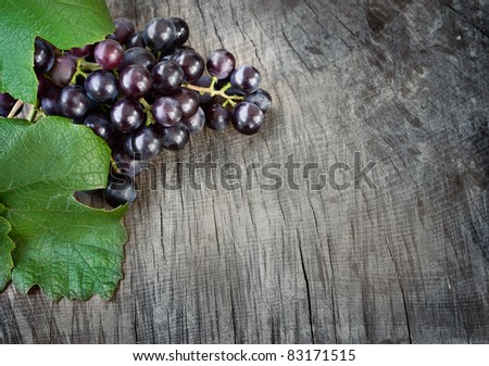 Freshly harvested Black grapes  on wooden background with copyspace - stock photo