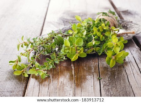 Freshly harvested bunch of thyme tied up with thread on wooden background