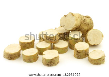 freshly harvested cut horseradish pieces on a white background - stock photo