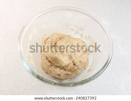 Freshly kneaded bread dough in a glass bowl on a kitchen work surface - stock photo