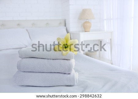 Freshly laundered fluffy towels in bedroom interior - stock photo