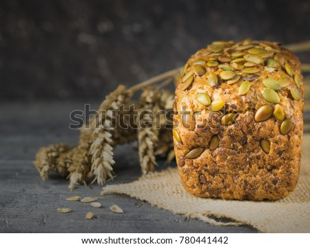 Freshly made bread from wheat flour with pumpkin seeds, sunflower and sesame seeds on the table. Background of ripe wheat ears.