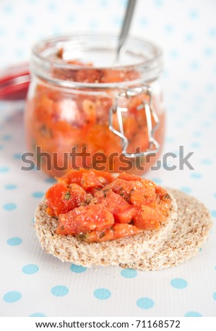 Freshly Made Bruschetta in Glass Jar with Toasted Whole Grain Bread - stock photo