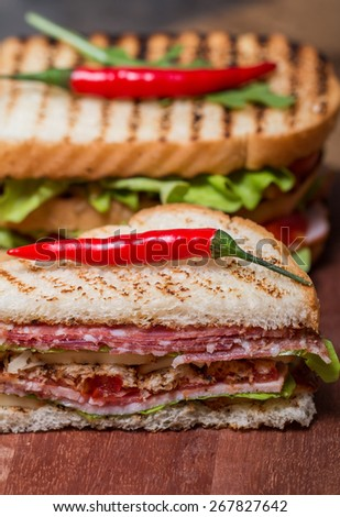 Freshly made club sandwiches served on a wooden chopping board - stock photo