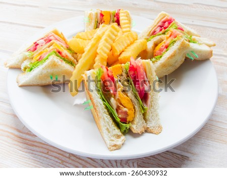 Freshly made clubsandwiches on wood table  - stock photo