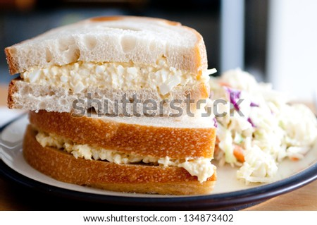 freshly made egg salad sandwiches on sourdough bread with a side of cole slaw - stock photo