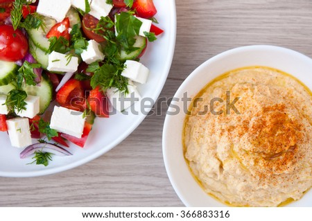 Freshly made Greek salad with vine ripened tomatoes and cubes of feta cheese. Served with home made hummus in white bowls. - stock photo