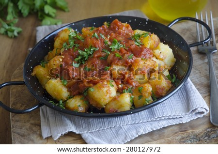 Freshly made patatas bravas topped with chopped parsley - stock photo