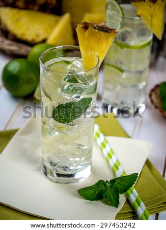 Freshly made pineapple mojito with ingredients setting