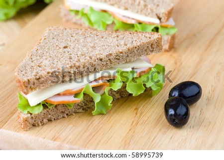 Freshly made sandwich with dietetic bread, ham and lettuce - stock photo